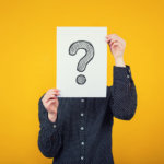 Businesswoman covering face using a white paper sheet with drawn question mark, like a mask, for hiding her identity. Isolated on yellow wall background. Introvert female anonymity concept.